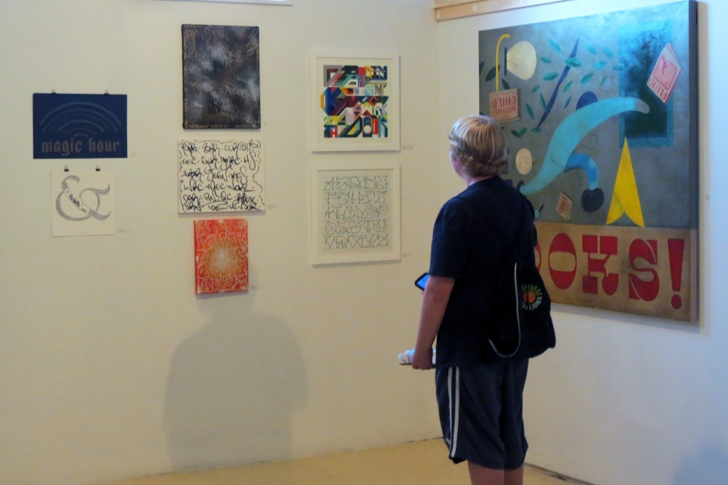 "A viewer looks at the work in ""Ode to Letters"" at Engine in Biddeford. Photo by the author."
